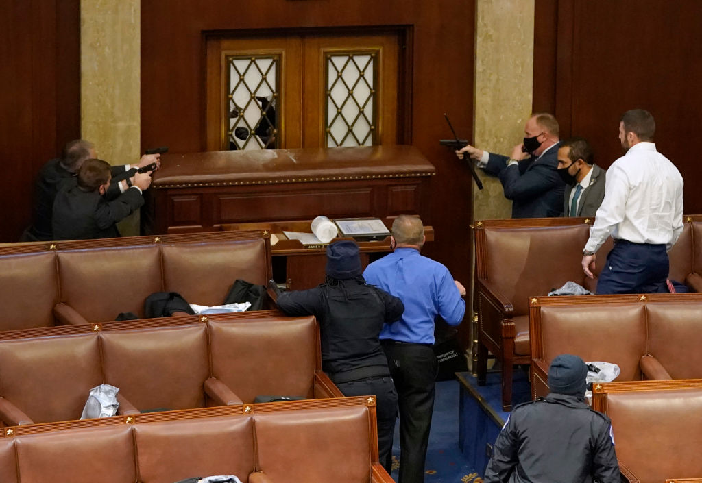 House security personnel point weapons at door to prevent pro-Trump rioters from breaching House chamber