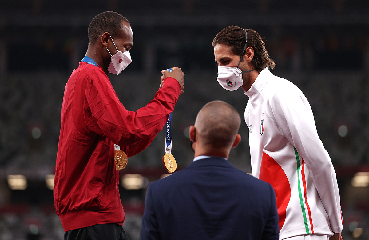 Joint gold medalists Mutaz Essa Barshim of Team Qatar presents Gianmarco Tamberi of Team Italy with his medal on the podium during the medal ceremony for the Mens High Jump on day ten of the Tokyo 2020 Olympic Games at Olympic Stadium on August 02 2021 in Tokyo Japan