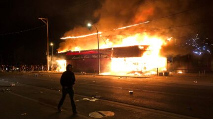 Flames rise from a liquor store near the Third Police Precinct on May 28, 2020 in Minneapolis, Minnesota, during a protest over the death of George Floyd, an unarmed black man, who died after a police officer kneeled on his neck for several minutes. - A police precinct in Minnesota went up in flames late on May 28 in a third day of demonstrations as the so-called Twin Cities of Minneapolis and St. Paul seethed over the shocking police killing of a handcuffed black man. The precinct, which police had abandoned, burned after a group of protesters pushed through barriers around the building, breaking windows and chanting slogans. A much larger crowd demonstrated as the building went up in flames.
